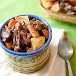 Pot roast with carrots and potatoes in ceramic bowl with spoon