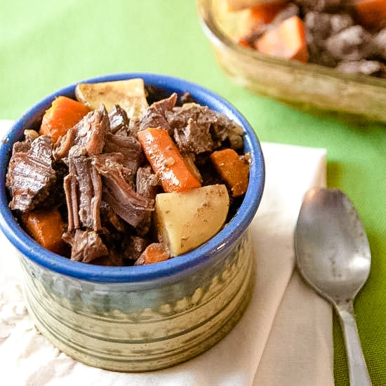 Pot roast with carrots and potatoes in a pottery bowl with a spoon