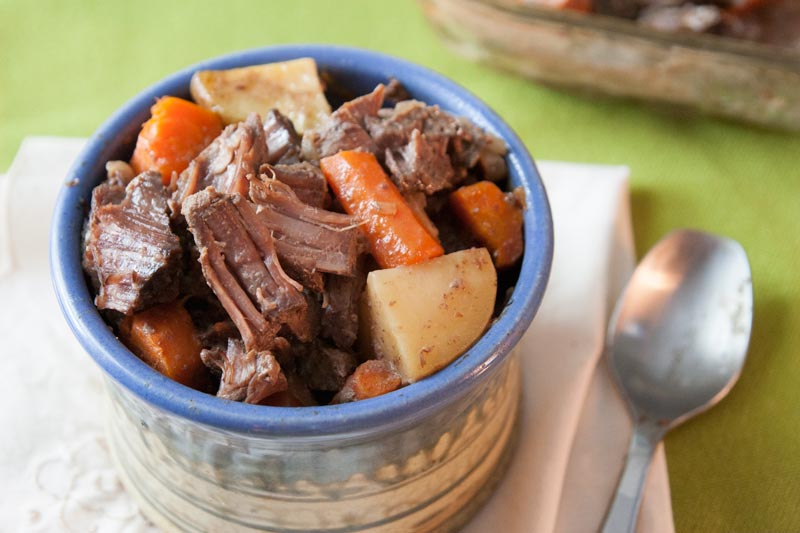 Pot roast with carrots and potatoes in hand-thrown ceramic bowl with spoon