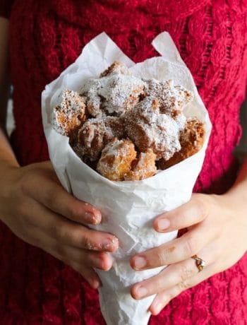 Woman in red sweater holding paper cone of zeppole (fried Italian donuts)