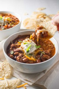 Hand holding tortilla chip scooping easy turkey chili from white bowl