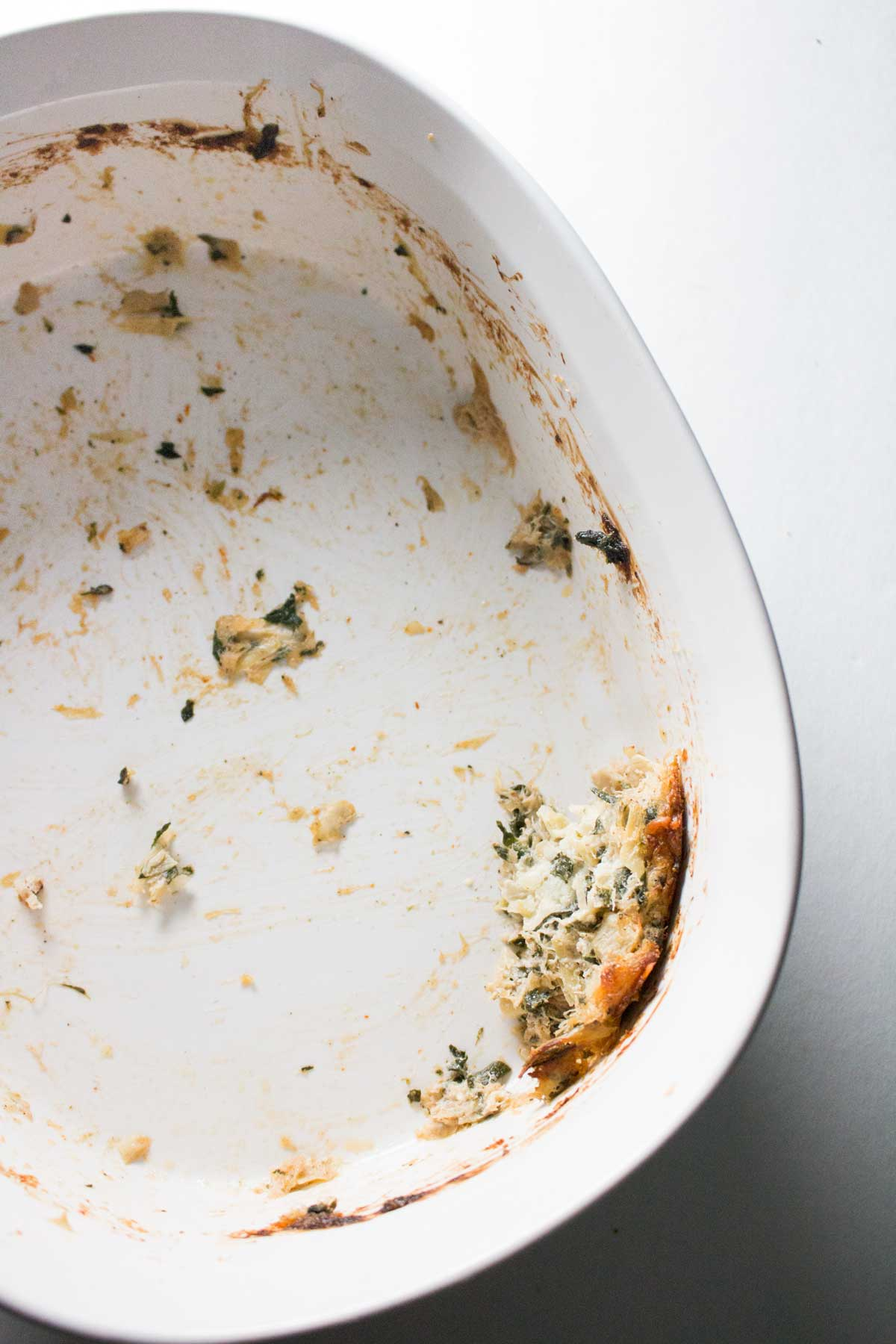 Empty casserole dish of spinach, artichoke, and crab dip