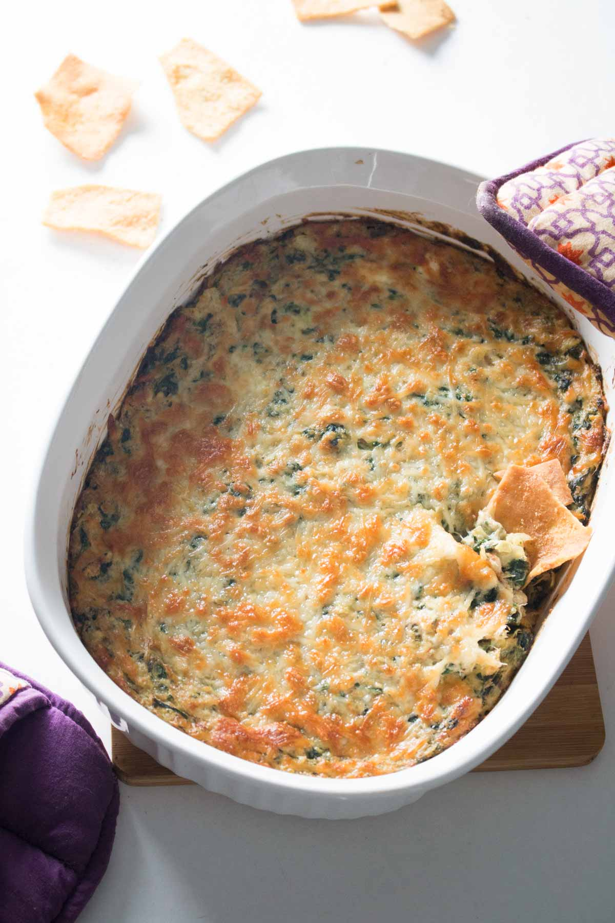 Overhead view of baked spinach, artichoke, and crab dip in white casserole dish