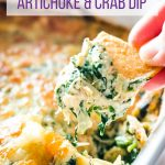 Closeup of baked spinach, artichoke, and crab dip scooped onto a pita chip