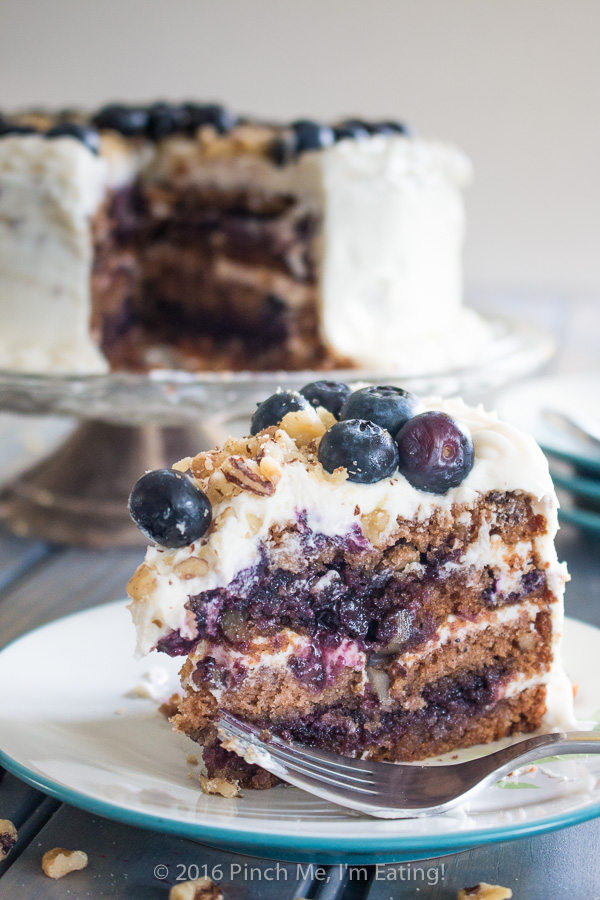 Blueberry spice cake with walnuts is layered with gooey blueberry jam and cream cheese frosting, and topped with walnuts and fresh berries for the perfect bite. A great cake for spring! | www.pinchmeimeating.com