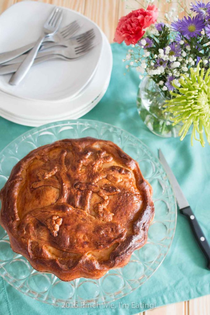 Italian Easter pie, or pizzagaina, on a cake stand with a tree made out of crust as decoration on the top of the pie.