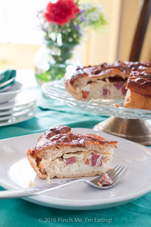 A slice of Italian Easter pie, or pizza rustica, on a white plate in front of the rest of the pie on a cake stand.