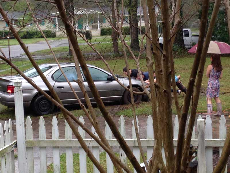 Three people pushing a stuck car out of the grass while woman in rain boots and umbrella looks on.