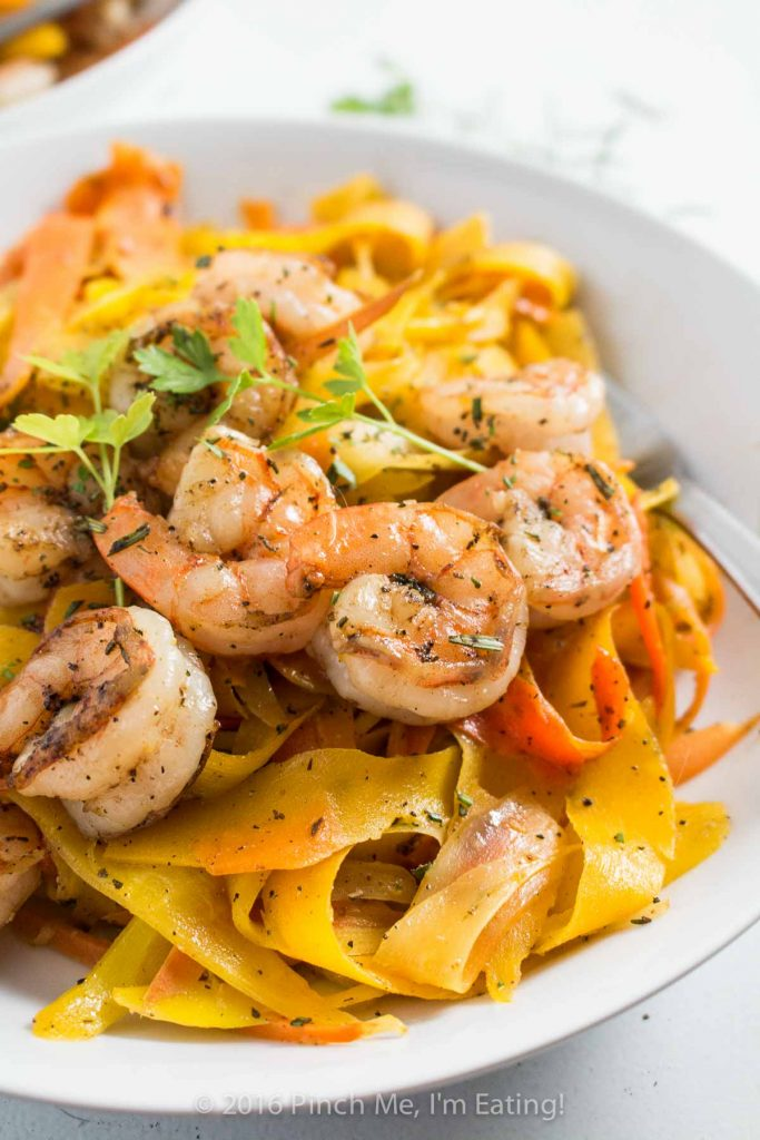 Delicate ribbons of carrots are tossed in browned butter with parsley, sage, rosemary, and thyme and topped with shrimp to make a fresh, flavorful, beautiful, and healthy meal. Carrot noodles are paleo and gluten free too! | www.pinchmeimeating.com