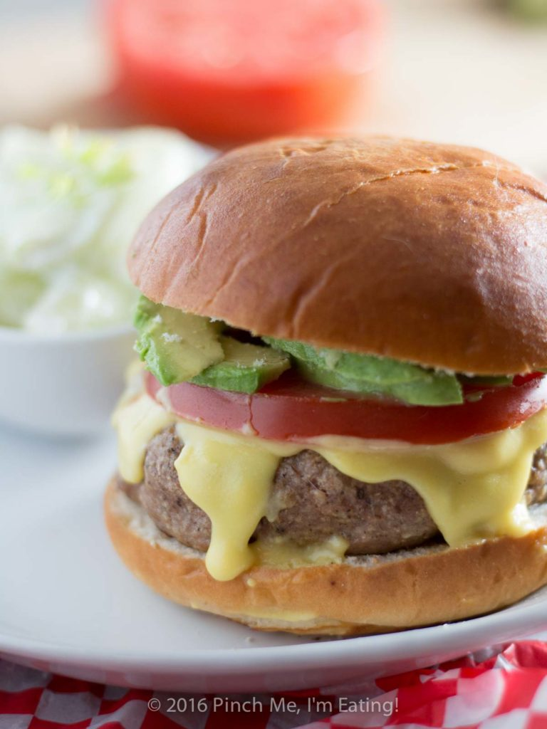 These juicy, aromatic gourmet turkey burgers topped with tomato, avocado, and Hollandaise sauce will make you feel like you're relaxing at an outdoor cafe! | www.pinchmeimeating.com