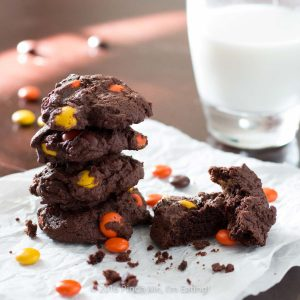 Chocolate Reese's cookies are cakey, brownie-like treats that are packed with peanut butter morsels and stay soft for days! With a rich brown chocolate cookie and orange and yellow Reese's Pieces, these cookies are full of fall colors and are perfect for autumn holidays!