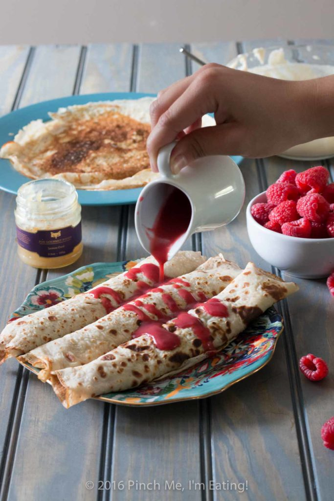 Lemon ricotta crêpes with raspberry sauce make an elegant brunch dish that's easier than it looks, and are a great way to use lemon curd! | www.pinchmeimeating.com