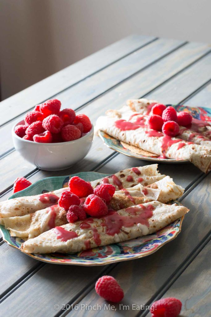 Lemon ricotta crêpes with raspberry sauce make an elegant brunch dish that's easier than it looks, and are a great way to use lemon curd!   www.pinchmeimeating.com