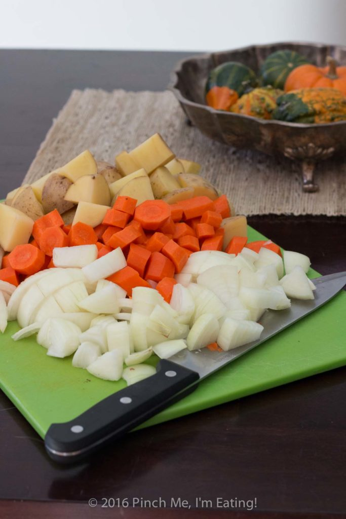 Potatoes, carrots, and onions cut up on cutting board for stove top beef stew