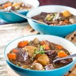 Beef stew with carrots, potatoes, and red wine in three blue bowls