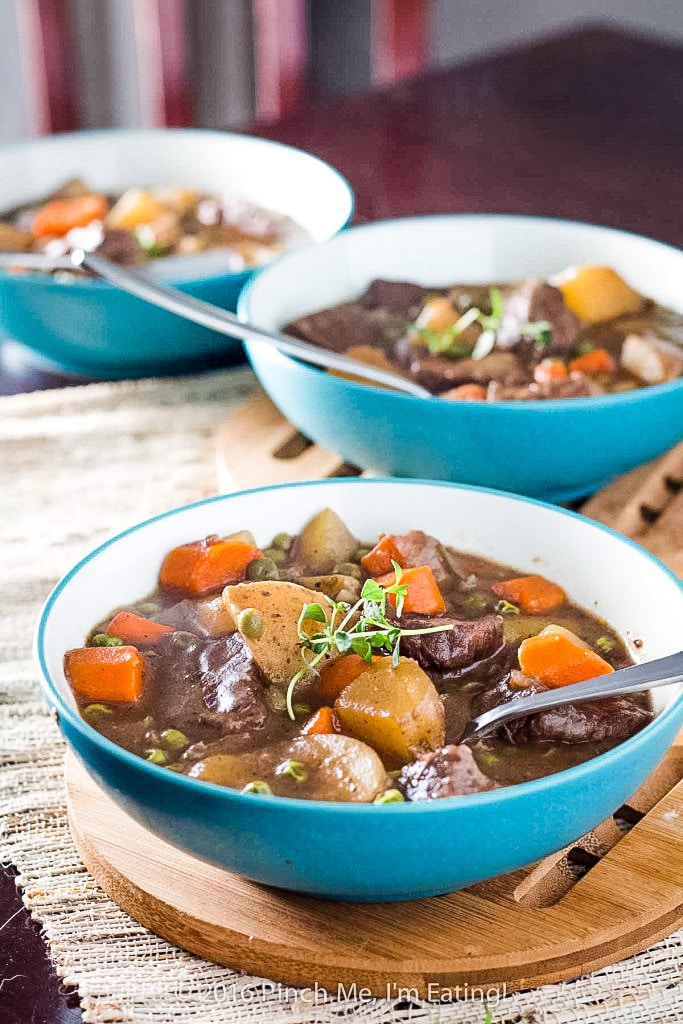 Stove top beef stew with carrots, potatoes, and red wine in three blue bowls