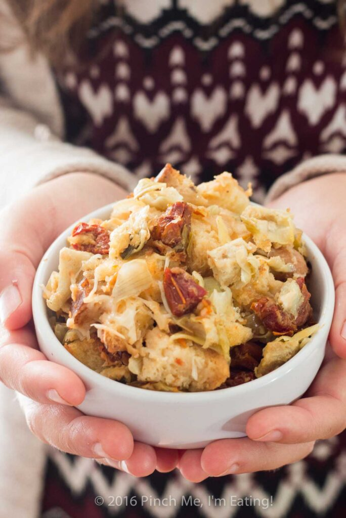 Sourdough sun-dried tomato artichoke stuffing with parmesan is a unique and delicious take on a holiday staple! This recipe is sure to be a crowd-pleaser this Thanksgiving or Christmas! | www.pinchmeimeating.com