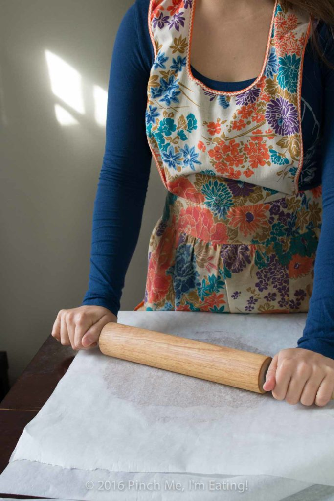 Woman with rolling pin in vintage flowered apron, rolling cookie dough between sheets of parchment paper