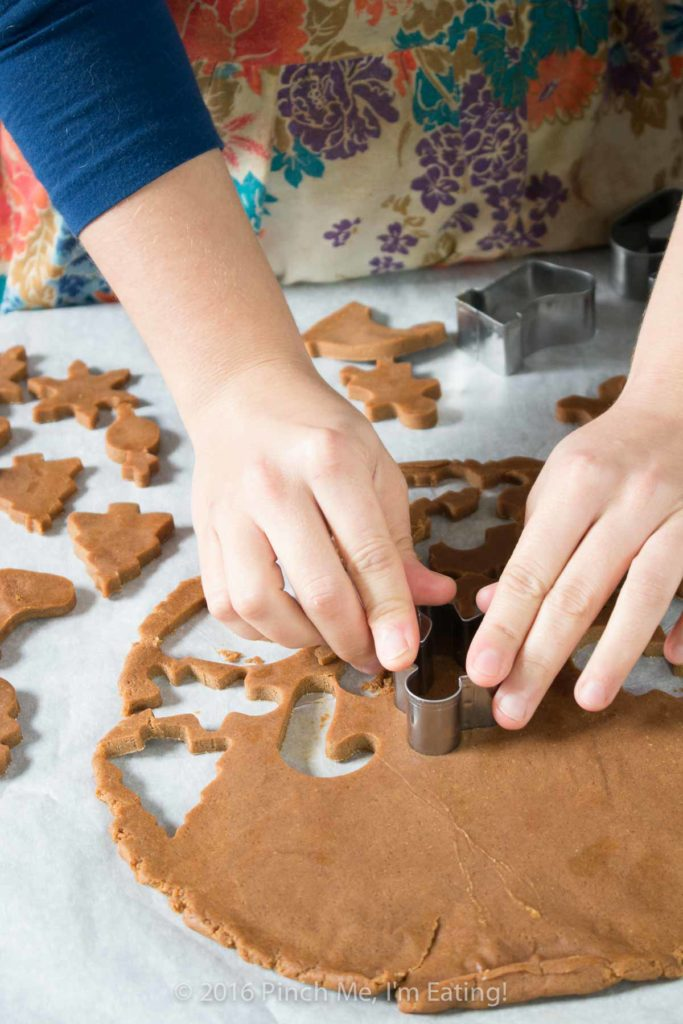 Woman in vintage flowered apron cutting out shapes for chewy gingerbread cookies with cookie cutters