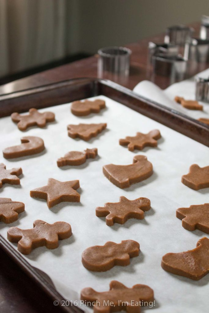Chewy gingerbread cookies and gingerbread men shapes on baking sheet waiting to be baked