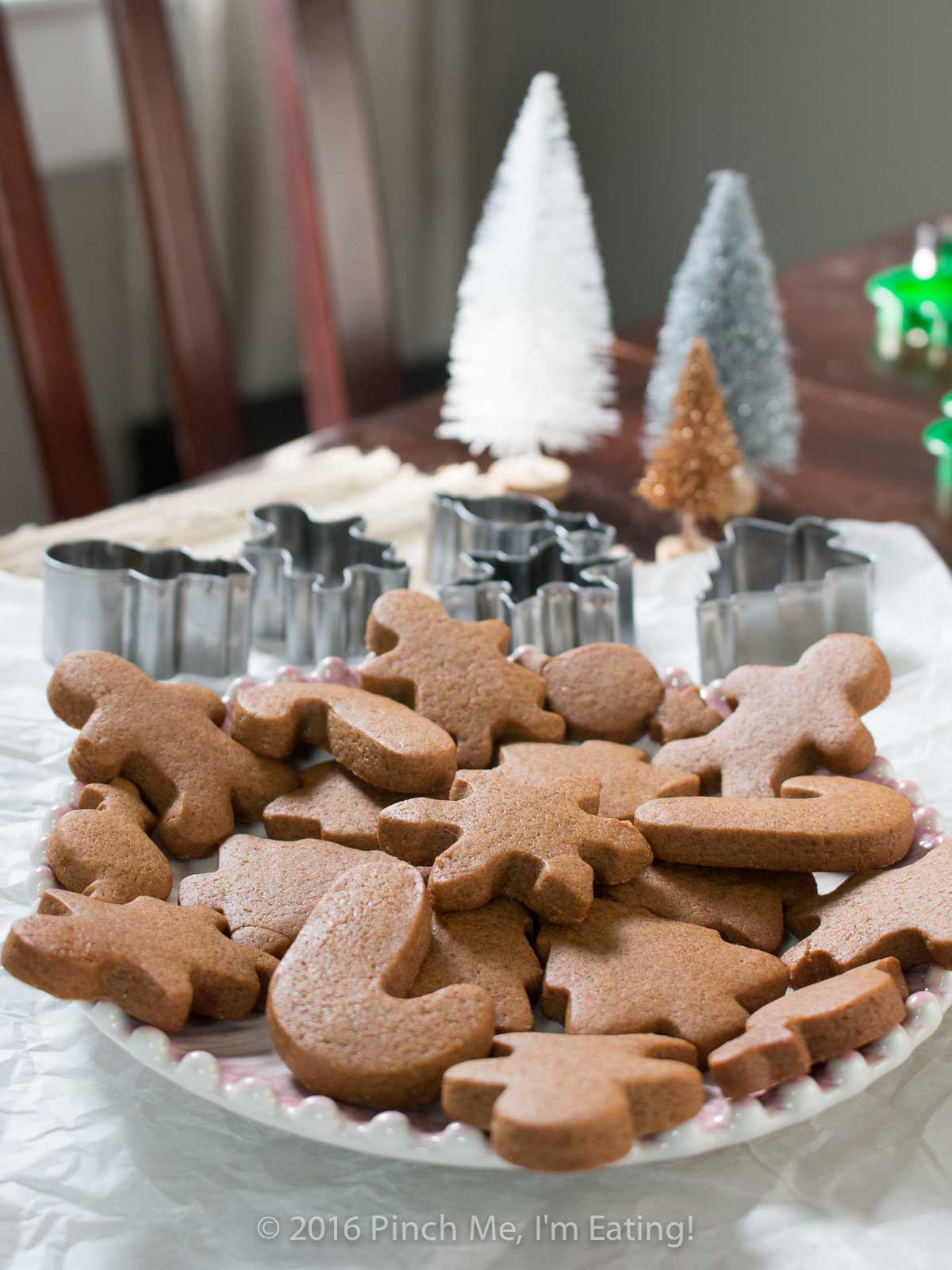 Chewy gingerbread cookies arranged on a plate with cookie cutters and Christmas trees in background