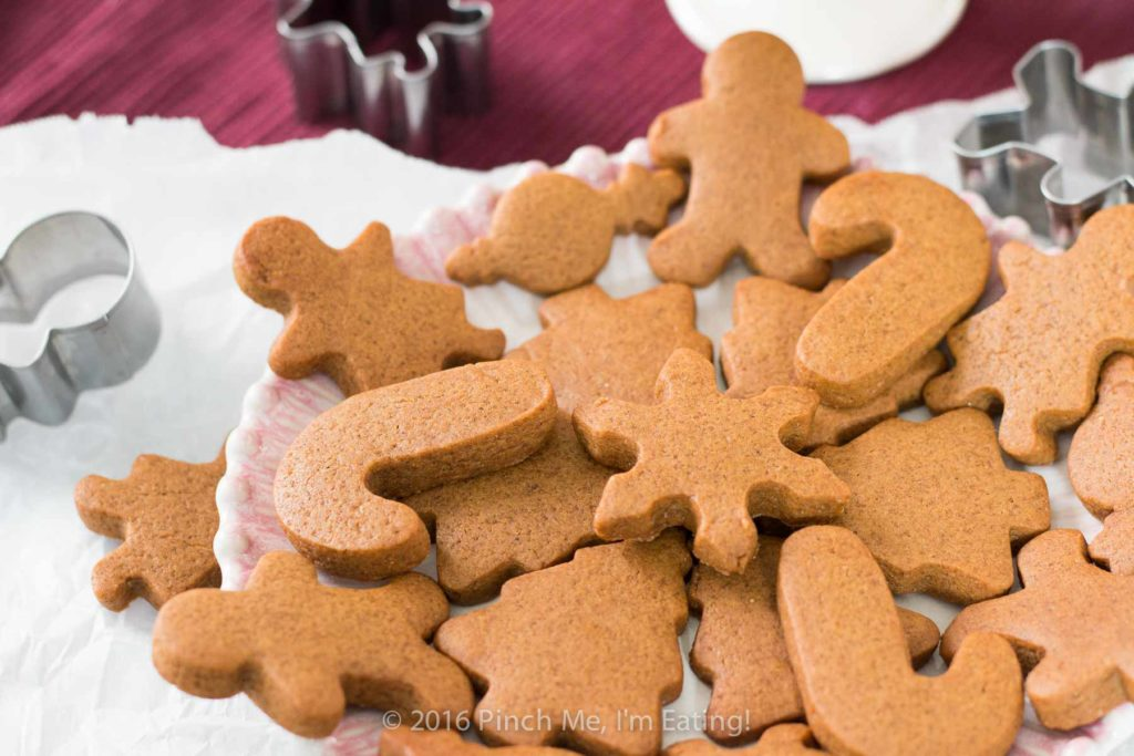 Chewy gingerbread men and other cutout cookies arranged on a plate with cookie cutters
