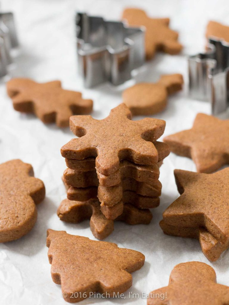 Chewy gingerbread snowflakes in a stack, surrounded by other gingerbread cookies and cookie cutters