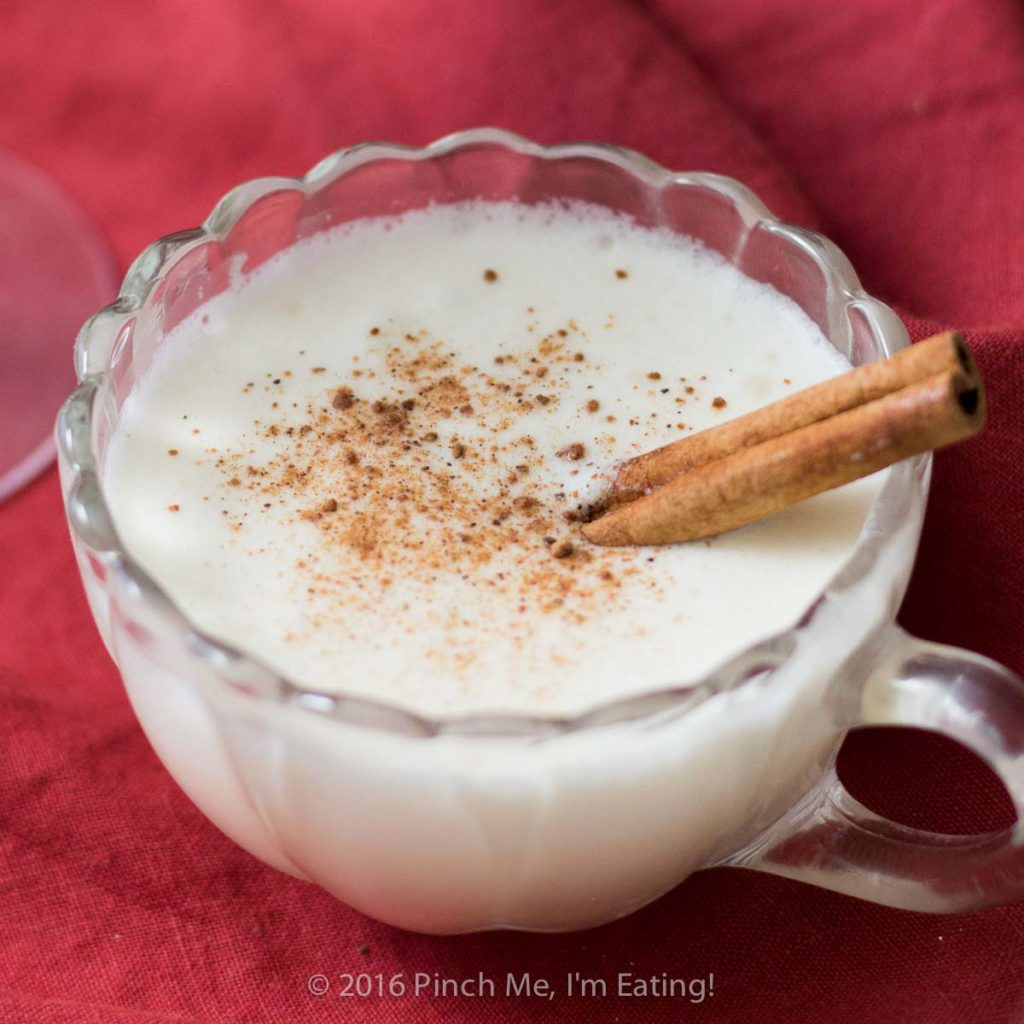 Three quarter view of homemade eggnog in a glass cup with cinnamon stick and nutmeg.