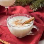 Homemade eggnog in a glass cup with cinnamon stick