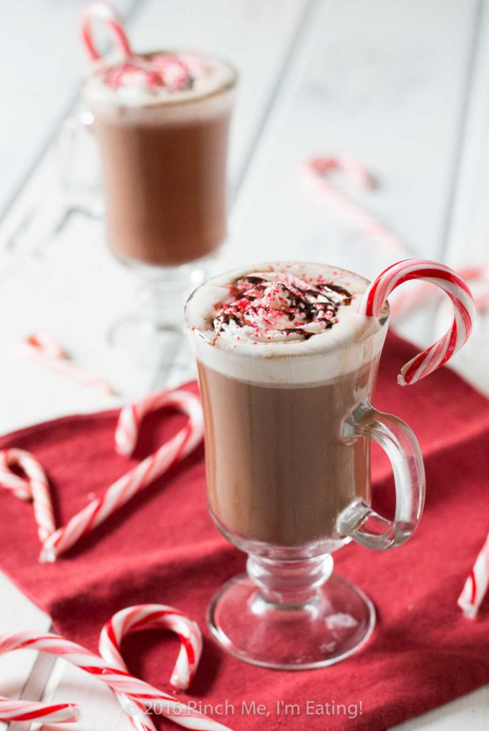 Two peppermint mocha lattes in clear glass mugs with whipped cream and candy canes on red napkin