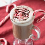Peppermint mocha in clear mug with candy canes on red napkin