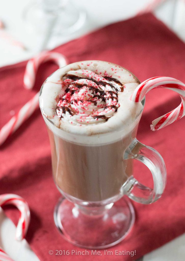 Peppermint mocha in clear glass mug with whipped cream and candy canes on red napkin