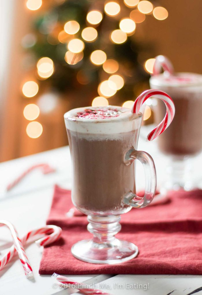 Peppermint mocha in clear glass mug with whipped cream and candy canes on red napkin. Blurred Christmas lights are in the background.
