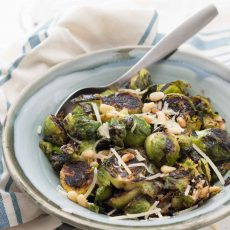 Pan-roasted lemon garlic Parmesan Brussels sprouts with pine nuts are an easy, healthy side dish you can make on the stove in about 15 minutes.