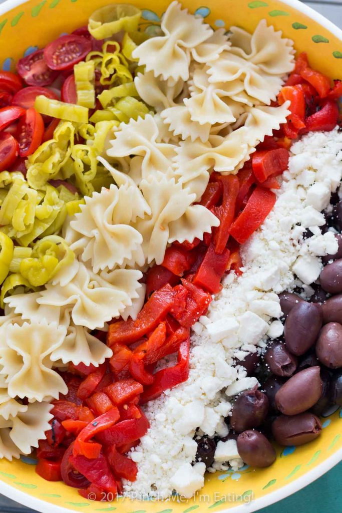Greek pasta salad recipe ingredients: feta cheese, pepperoncinis, kalamata olives, tomatoes, and roasted red peppers