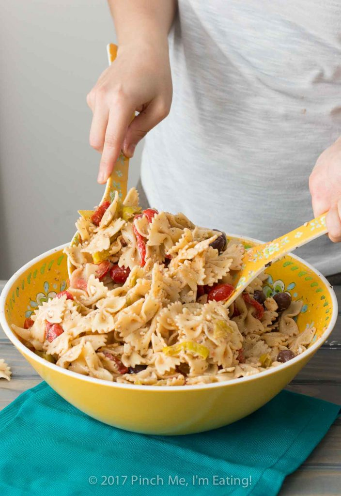 Tossing pasta salad with Greek dressing