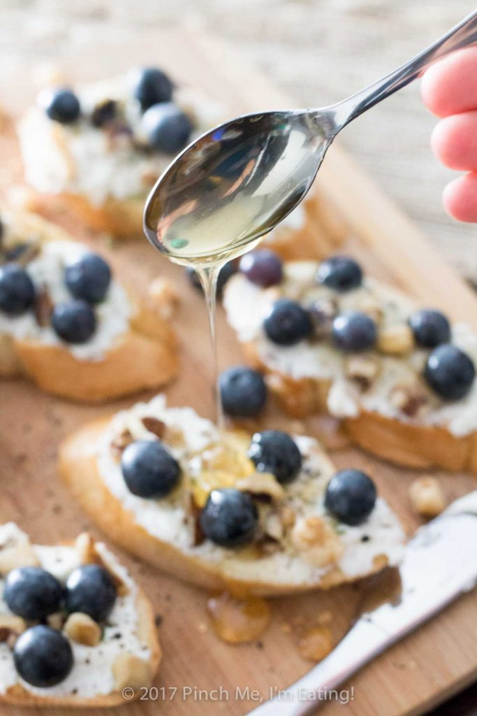 Ricotta crostini with blueberries, walnuts, honey, and thyme is an unexpected and delightful appetizer perfect for serving with wine and cheese!