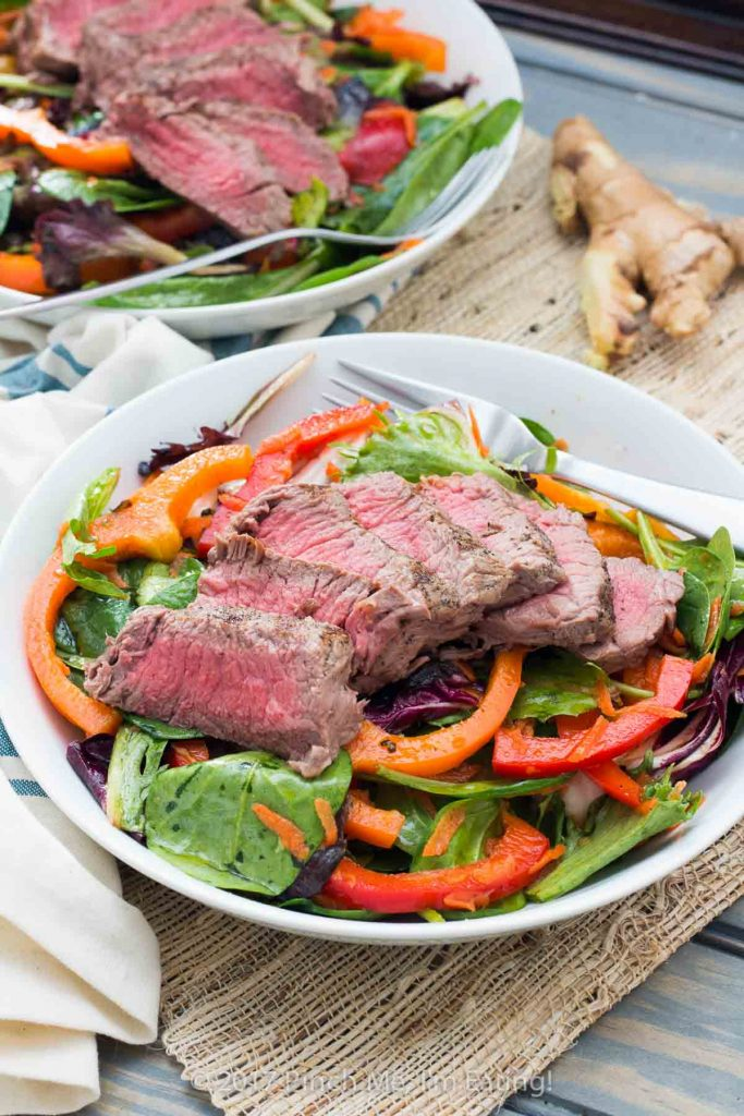 This mixed greens salad with bell peppers and a soy ginger vinaigrette is topped with a rare steak for a light and refreshing spring or summer lunch!