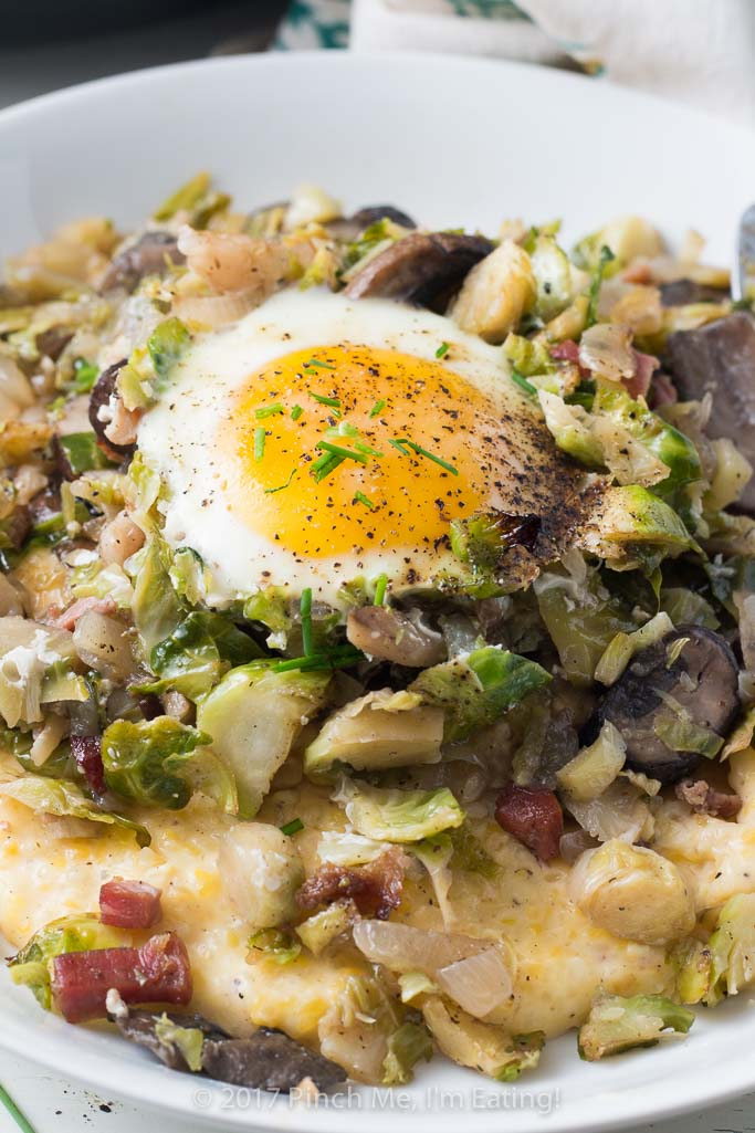Brussels sprout hash with pancetta, mushrooms, and an egg on top is perfect for breakfast OR dinner, served with cheesy grits!
