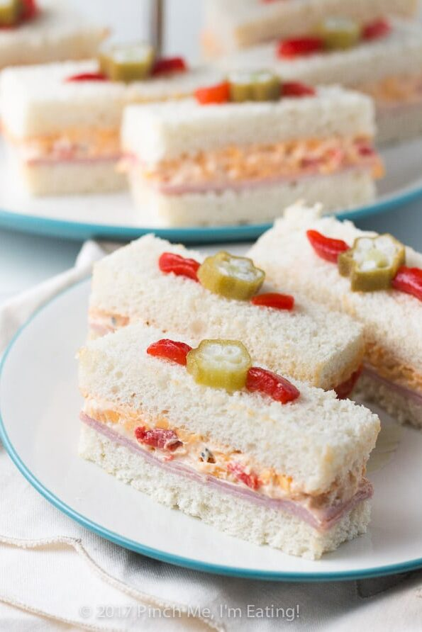 Ham and pimento cheese tea sandwiches topped with pickled okra garnish