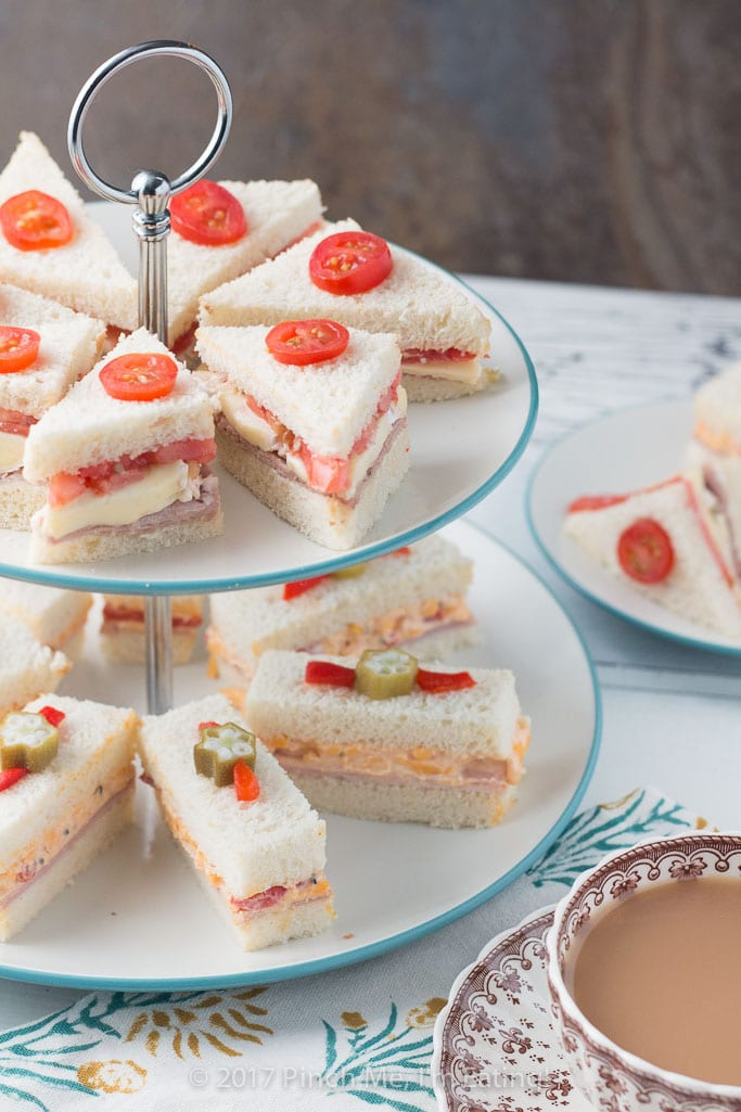 These adorable ham and pimento cheese tea sandwiches would be perfect for a Southern tea party or afternoon tea! And they're topped with the cutest pickled okra garnishes!
