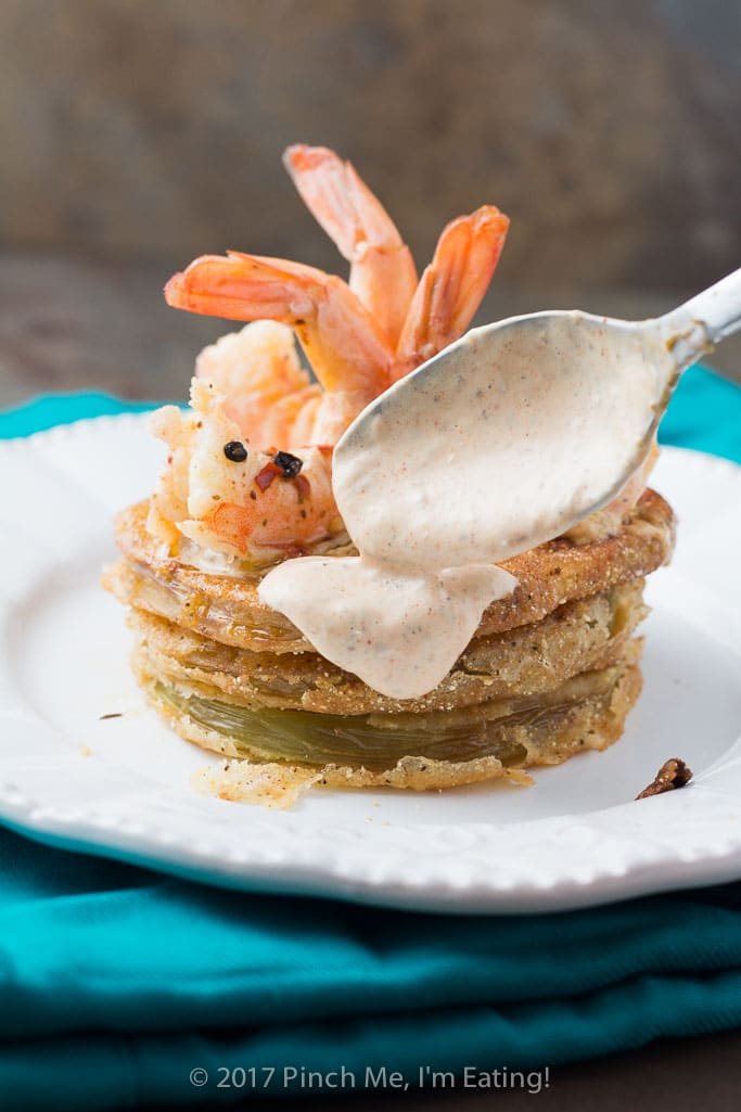 Spooning on remoulade: Fried green tomatoes with Cajun remoulade and pickled shrimp combine into a tangy, spicy, and crispy Southern dish you can use as an appetizer, side dish, or entrée!