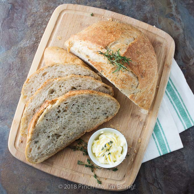Rosemary thyme no-knead Dutch oven bread is airy and soft on the inside with a glossy crust that shatters when you cut into it - the perfect crusty bread for stew or just dipping into olive oil! Best of all, you hardly have to do anything to make it!