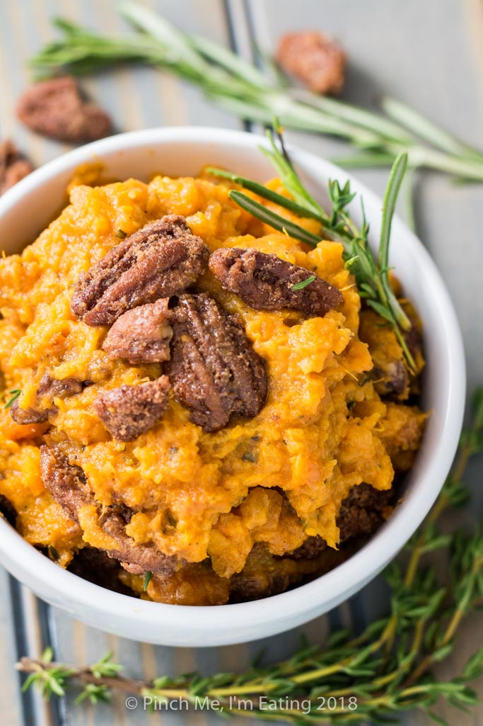 Closeup of rosemary mashed sweet potatoes with pecans candied in cinnamon sugar in white bowl, with sprig of fresh rosemary