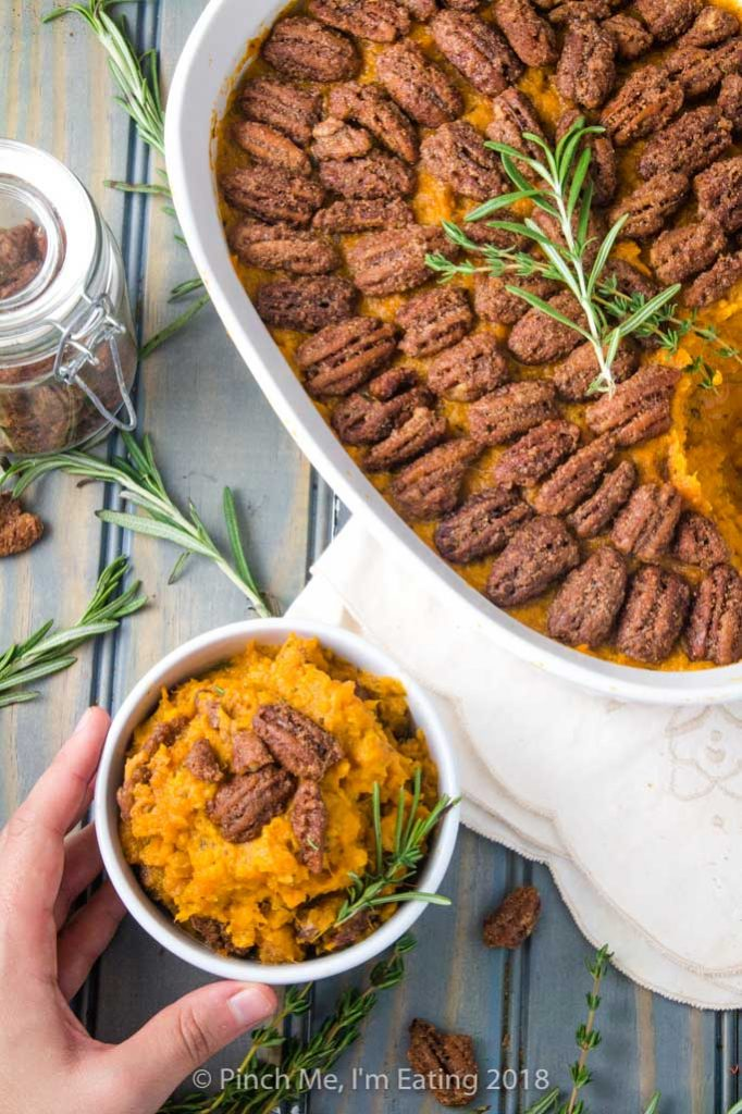 Overhead shot of sweet potato casserole in white serving dish and small white bowl, topped with candied pecans and rosemary