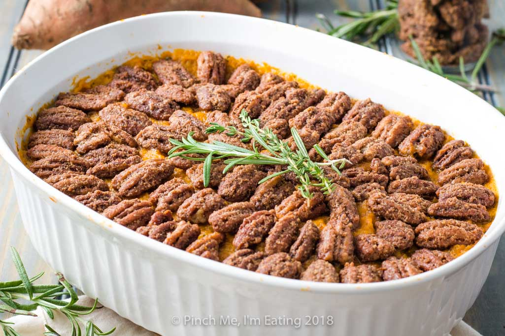 Sweet potato casserole with pecans candied in cinnamon sugar in white serving dish, topped with rosemary