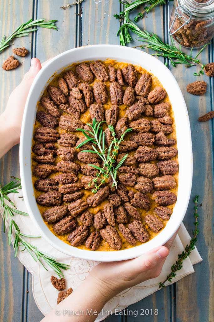 Overhead shot of sweet potato casserole with pecans candied in cinnamon sugar in white serving dish, topped with rosemary