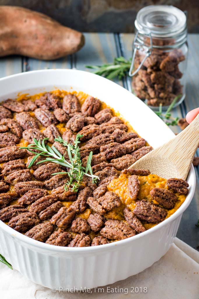 Spoon serving sweet potato casserole with pecans candied in cinnamon sugar from white serving dish, topped with rosemary