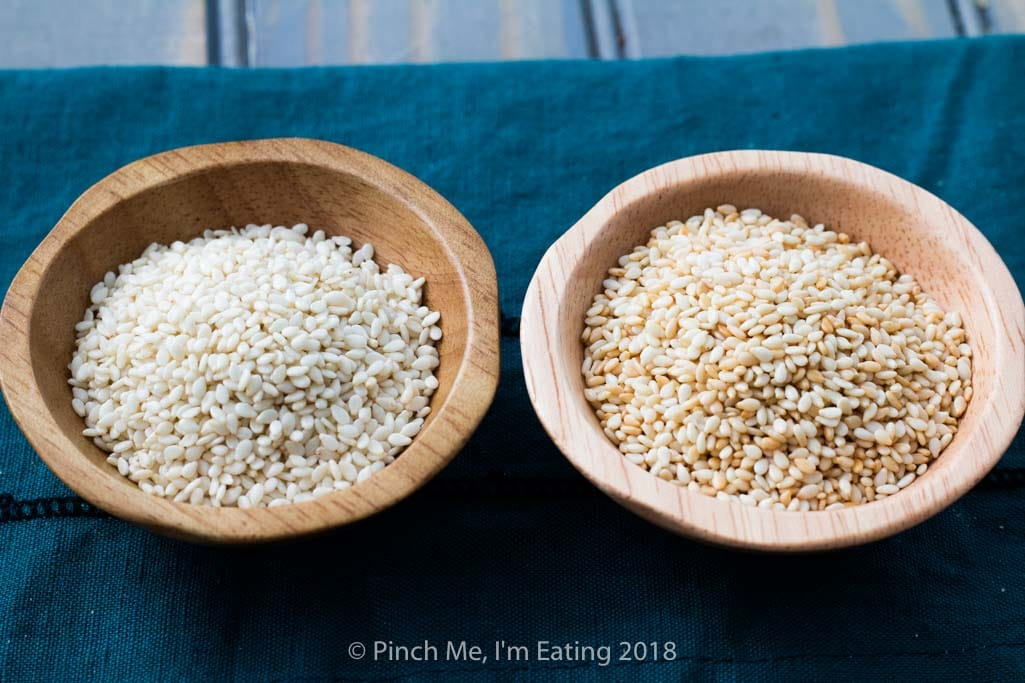 Small wooden bowls of untoasted and toasted sesame seeds for making benne wafers