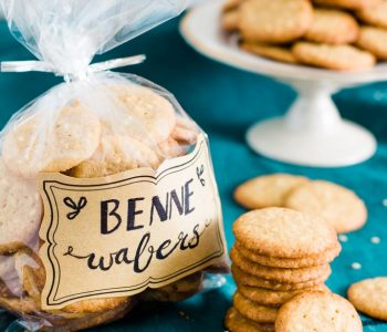 Benne wafers stacked surrounding cellophane bag of benne wafers